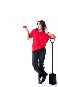Widok z przodu młoda kobieta trzymająca czarną łopatę i kartę bankową na białym tle kobieta praca gleba praca kopanie ziemi noc kolory pieniądze