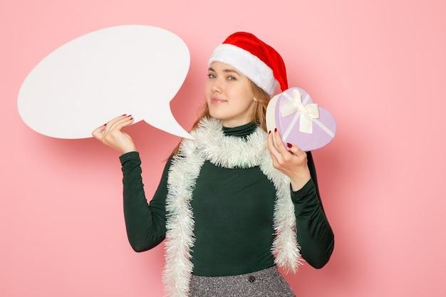 Widok z przodu młoda kobieta trzymająca duży biały znak i obecna na różowej ścianie model wakacje boże narodzenie nowy rok kolor emocji
