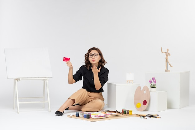 Widok z przodu młoda kobieta trzymająca kartę bankową na jasnym tle