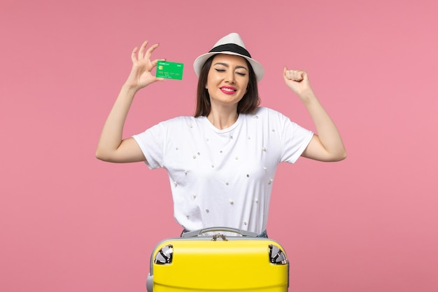 Widok z przodu młoda kobieta trzymająca kartę bankową na różowej ścianie emocja letnia wycieczka kobieta