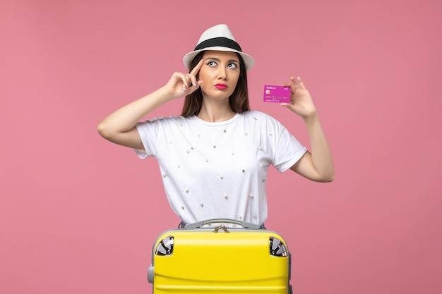 Widok z przodu młoda kobieta trzymająca kartę bankową na różowej ścianie wakacje kobieta wycieczka pieniądze
