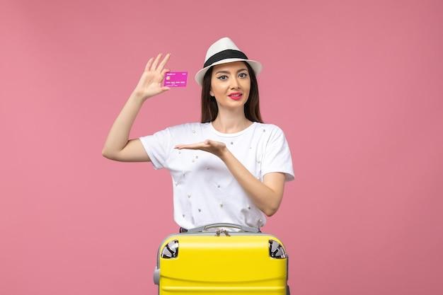 Widok z przodu młoda kobieta trzymająca kartę bankową na różowej ścianie wycieczka kolor pieniędzy wakacje