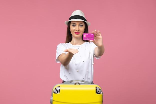 Widok z przodu młoda kobieta trzymająca kartę bankową na różowej ścianie wycieczki wakacje kobieta pieniądze