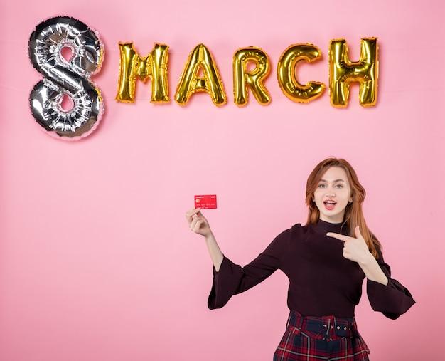 Widok z przodu młoda kobieta trzymająca kartę bankową na różowych wakacjach zakupowych