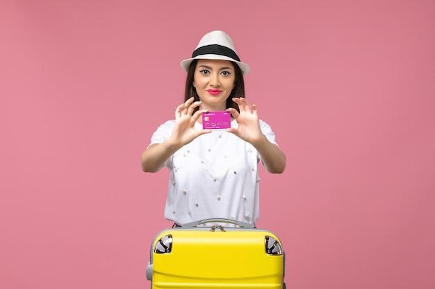 Widok z przodu młoda kobieta trzymająca kartę bankową na różowym biurku podróż kolor pieniędzy wakacje