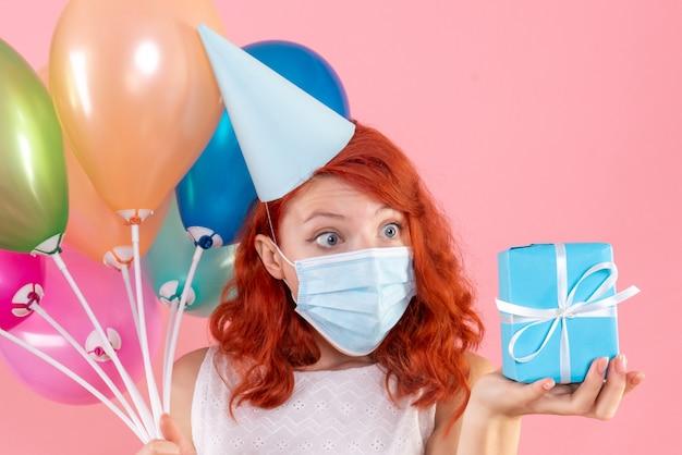 Widok z przodu młoda kobieta trzymająca kolorowe balony i mały prezent na różowym biurku xmas kolor foto party covid virus