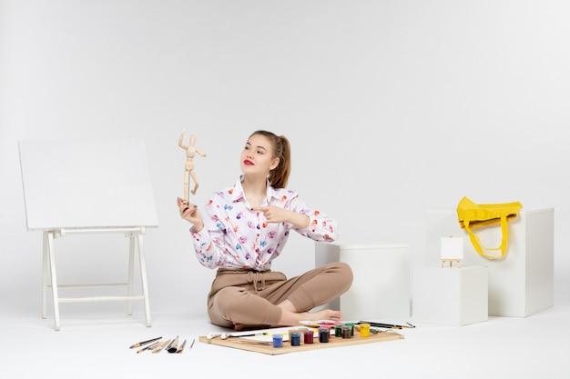 Widok z przodu młoda kobieta trzymająca zabawkową postać ludzką na białym tle
