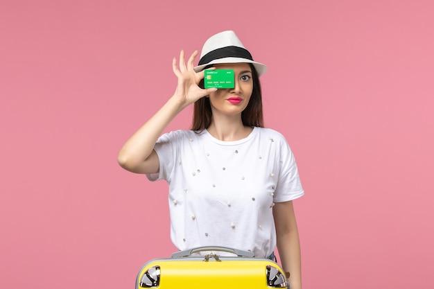 Widok z przodu młoda kobieta trzymająca zieloną kartę bankową na różowej ścianie emocji letniej kobiety podróży