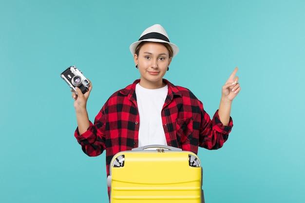 Widok z przodu młoda kobieta udająca się w podróż i trzymając aparat na jasnoniebieskiej przestrzeni