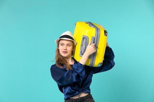 Widok z przodu młoda kobieta udaje się na wakacje i trzyma dużą torbę na jasnoniebieskim biurku podróż morska podróż wakacyjna