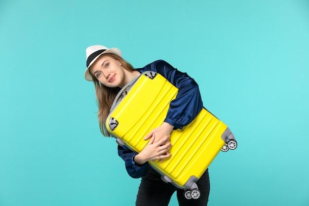 Widok z przodu młoda kobieta udaje się na wakacje i trzyma dużą torbę na niebieskim tle podróż podróż wakacje samolot rejs morski