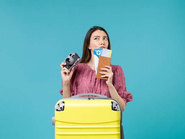Widok z przodu młoda kobieta udaje się na wakacje trzymając aparat i bilety na jasnoniebieskim tle podróż wakacje kobieta morze za granicą
