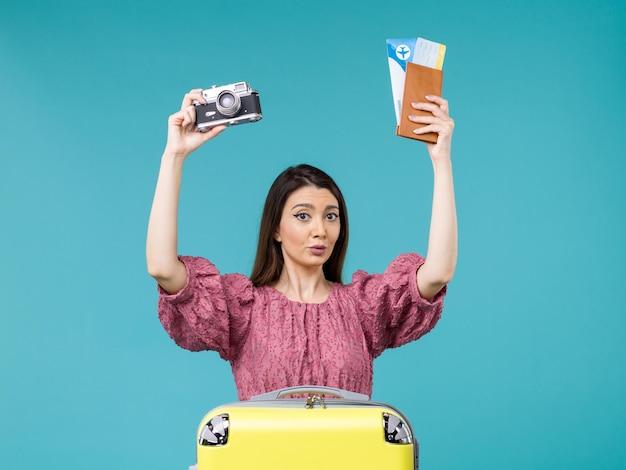 Widok z przodu młoda kobieta udaje się na wakacje trzymając aparat i bilety na niebieskim tle podróż wakacje kobieta morze za granicą