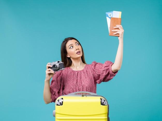 Widok z przodu młoda kobieta udaje się na wakacje trzymając aparat i bilety na niebieskim tle podróż wakacje kobieta za granicą morze