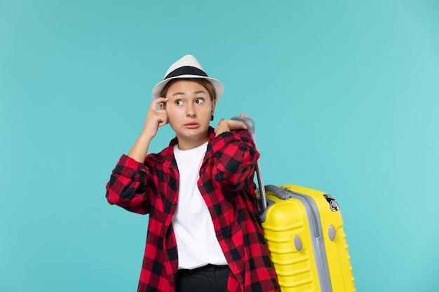 Widok z przodu młoda kobieta udaje się na wakacje z żółtą torbą na niebieskim polu