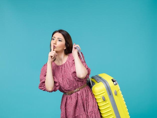 Widok z przodu młoda kobieta udaje się na wakacje ze swoją żółtą torbą na niebieskim tle podróż wycieczka letnia kobieta człowiek morski