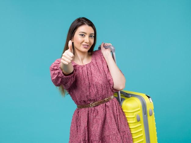Widok z przodu młoda kobieta udaje się na wakacje ze swoją żółtą torbą uśmiechając się na niebieskim tle podróż wycieczka letnia kobieta człowiek morski