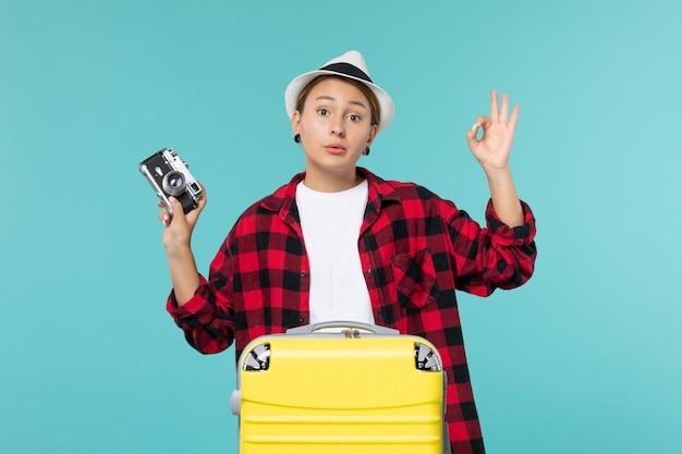 Widok z przodu młoda kobieta udaje się w podróż i trzyma aparat na jasnoniebieskiej przestrzeni