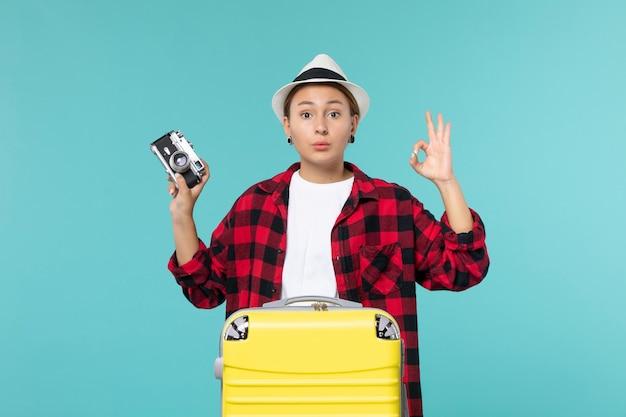 Widok z przodu młoda kobieta udaje się w podróż i trzyma aparat na niebieskiej podłodze podróż samolot rejs kobieta morze