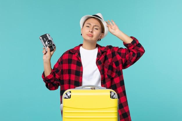 Widok z przodu młoda kobieta udaje się w podróż i trzyma aparat na niebieskiej przestrzeni