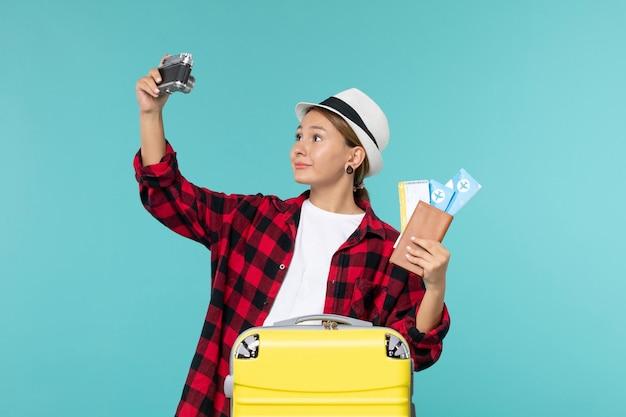 Widok z przodu młoda kobieta udaje się w podróż trzymając bilety i aparat na niebieskiej przestrzeni
