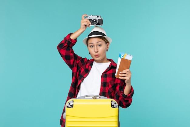 Widok Z Przodu Młoda Kobieta Udaje Się W Podróż Trzymając Bilety I Aparat Na Niebieskiej Przestrzeni Darmowe Zdjęcia