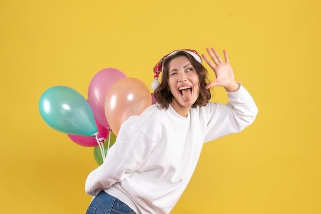 Widok z przodu młoda kobieta ukrywa kolorowe balony na żółty nowy rok boże narodzenie kolor wakacje kobieta emocja