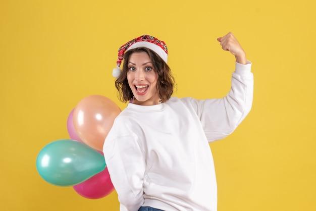 Widok z przodu młoda kobieta ukrywa kolorowe balony na żółtym biurku nowy rok boże narodzenie kolor wakacje kobieta emocja