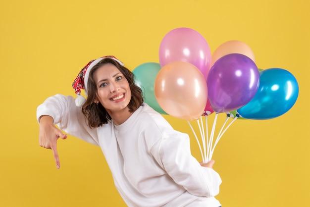Widok z przodu młoda kobieta ukrywa kolorowe balony nowy rok boże narodzenie kolor wakacje kobieta emocja