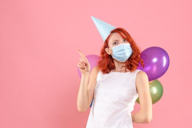 Widok z przodu młoda kobieta ukrywa kolorowe balony w sterylnej masce na różowym tle party covid- kolor boże narodzenie nowy rok