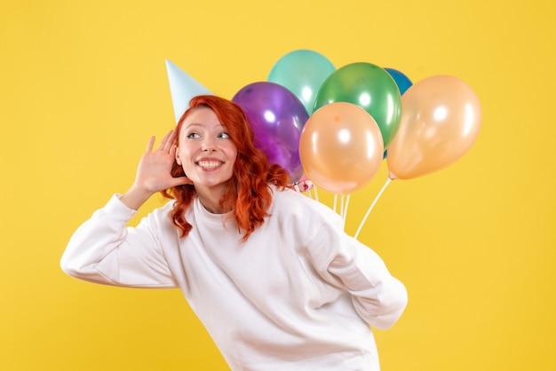 Widok z przodu młoda kobieta ukrywa kolorowe balony za plecami kolor nowy rok emocje party xmas woman