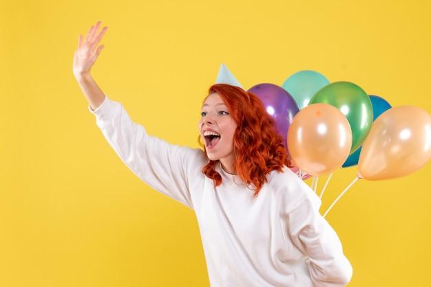 Widok z przodu młoda kobieta ukrywa kolorowe balony za plecami kolor nowy rok
