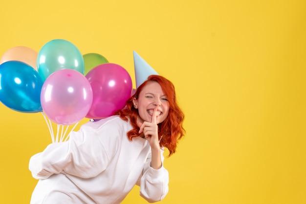Widok z przodu młoda kobieta ukrywa kolorowe balony za plecami nowy rok emocji kolor xmas kobieta