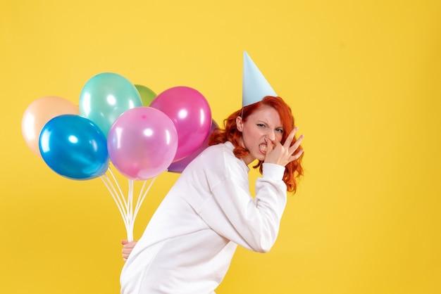 Widok z przodu młoda kobieta ukrywa kolorowe balony za plecami nowy rok