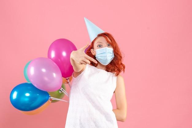 Widok z przodu młoda kobieta ukrywa kolorowe balony za plecami w sterylnej masce na różowym tle party covid - kolor bożonarodzeniowy nowy rok