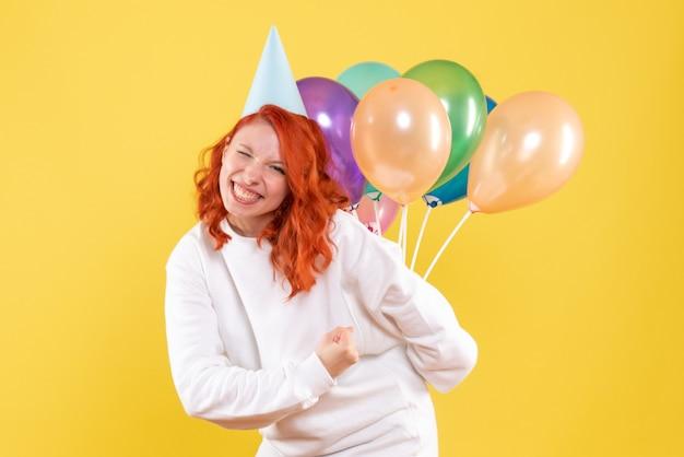 Widok z przodu młoda kobieta ukrywa kolorowe balony za plecami xmas kolor nowy rok emocja strona kobieta