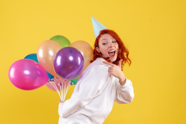 Widok z przodu młoda kobieta ukrywa śliczne kolorowe balony na żółto