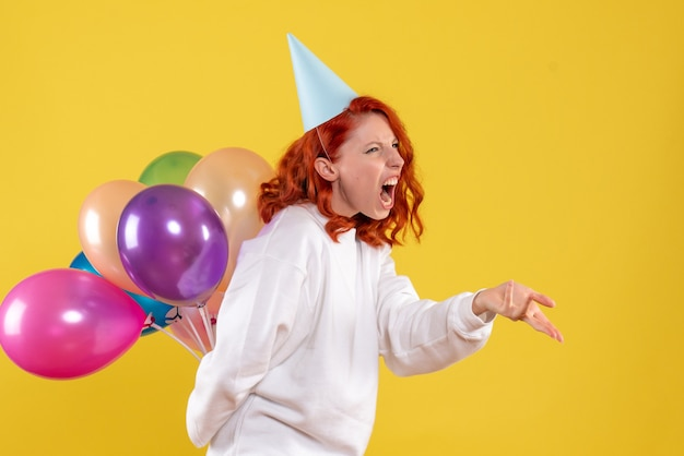 Widok z przodu młoda kobieta ukrywa słodkie kolorowe balony na żółtym tle kobieta kolor emocji strony nowego roku