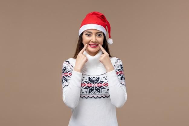 Widok z przodu młoda kobieta uśmiecha się na brązowym tle emocji boże narodzenie nowy rok