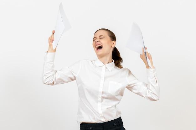 Widok z przodu młoda kobieta w białej bluzce trzymająca dokumenty i czująca złość na białym tle kobiece emocje pracy czujące biuro
