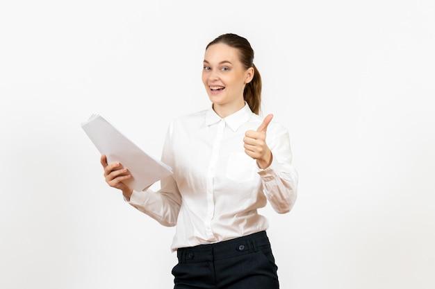 Widok z przodu młoda kobieta w białej bluzce trzymająca dokumenty i uśmiechająca się na białym tle kobiece emocje pracy czujące biuro