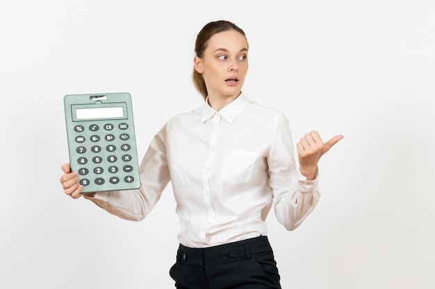 Widok z przodu młoda kobieta w białej bluzce trzymająca duży kalkulator na białym tle biuro kobiece emocje uczucia praca pracownik biały