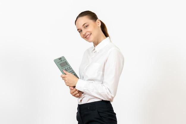 Widok z przodu młoda kobieta w białej bluzce trzymająca duży kalkulator na białym tle biuro kobiece emocje uczucie praca pracownik biały