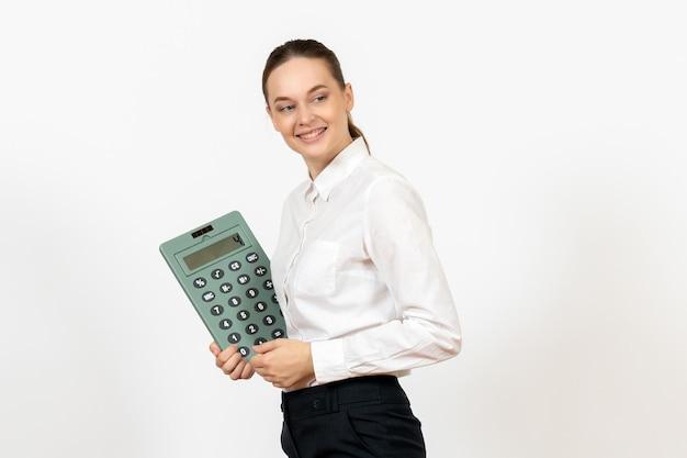 Widok z przodu młoda kobieta w białej bluzce trzymająca ogromny kalkulator na białym tle biuro kobiece emocje uczucie praca pracownik biały