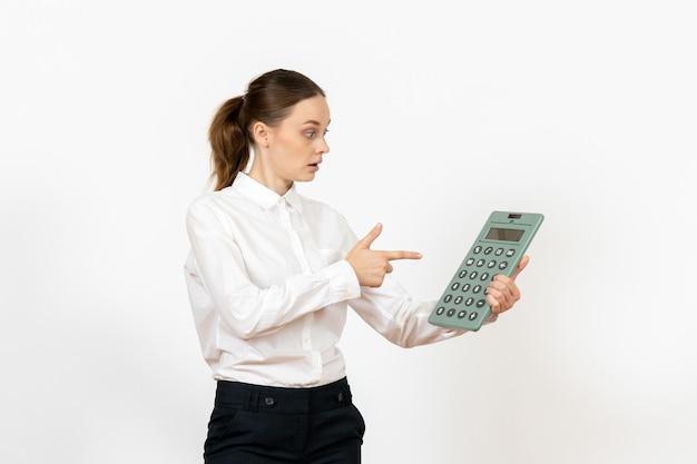 Widok z przodu młoda kobieta w białej bluzce trzymająca ogromny kalkulator na białym tle kobiece emocje uczucie praca biurowa