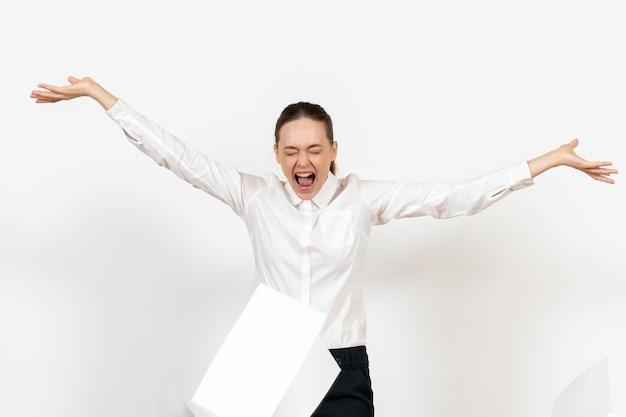 Widok z przodu młoda kobieta w białej bluzce ze złością rzucająca plikami na białym tle kobiece emocje uczucie praca biurowa