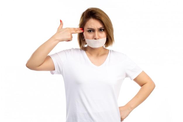 Widok z przodu młoda kobieta w białej koszulce i czarnych dżinsach z białym bandażem wokół ust, pokazująca broń do głowy na białym