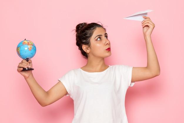 Widok z przodu młoda kobieta w białej koszulce i dżinsach, trzymając papierowy samolot i mały glob