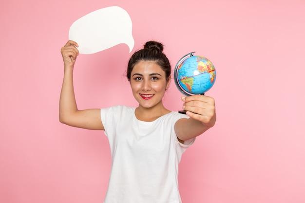Widok z przodu młoda kobieta w białej koszulce i niebieskich dżinsach pozuje z uśmiechem trzymając mały glob i biały znak