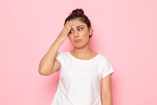 Widok z przodu młoda kobieta w białej koszulce i niebieskich dżinsach pozuje z zdezorientowanym wyrazem twarzy